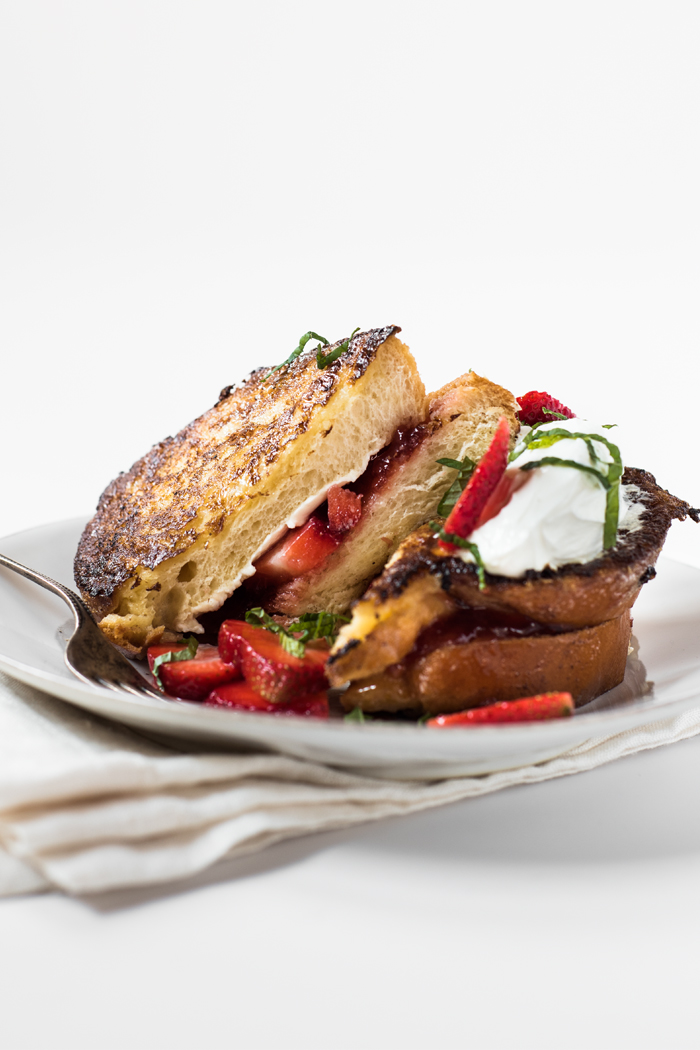 This French Toast sandwich (if you will), is stuffed with cream cheese, strawberry preserves, and macerated fresh strawberries. Topped with sour cream, more strawberries, and fresh mint – it's like an orgasim in your mouth!