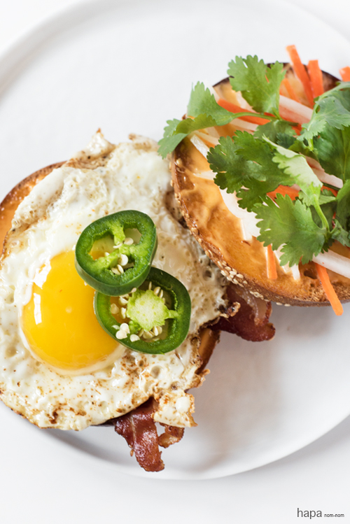 Breakfast-Banh-Mi on a bagel with crispy bacon and fried egg.
