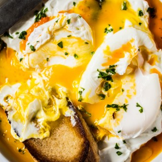 Dense garlicky yogurt swirled into a spiced butter and the richness of a poached egg. Dip a warm piece of toasted rustic bread into the golden sunrise of colors, and you've got heaven on a plate.