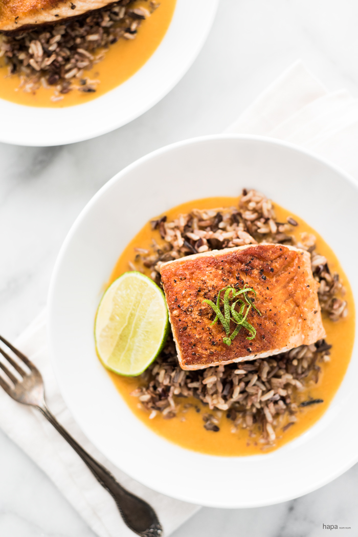 Pan seared salmon on a bed of wild rice in a rich and creamy ginger and coconut curry broth.