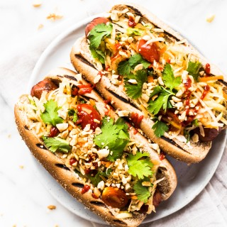 These Thai Style Hot Dogs are a fantastic twist on an American classic. Topped with cool papaya salad, crunchy peanuts, and spicy Sriracha.